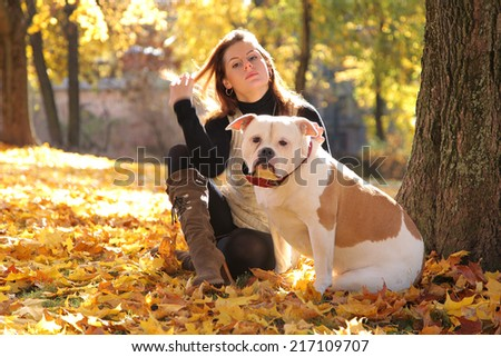 young woman relaxing in autumn park with dog