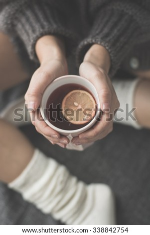 Young woman relaxing in bed with a cup of tea