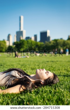 Young woman relaxing in Central Park laying on the grass and listening to music. New York City. Filtered image. - stock photo