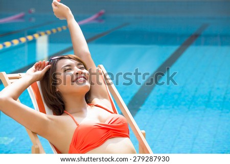 young woman relaxing in  chair beside swimming pool - stock photo