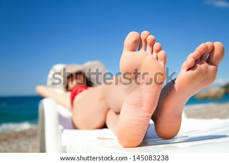 Young woman relaxing in chaise  on the beach - stock photo