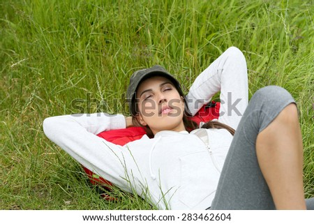 Young woman relaxing in grass on hiking day