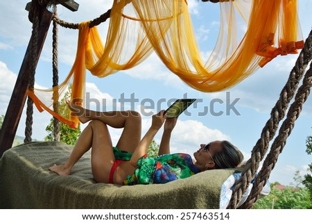 young woman relaxing in hammock with tablet - stock photo