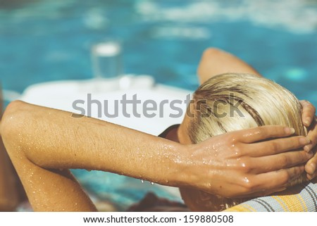 Young woman relaxing in pool on a hot summers day - stock photo