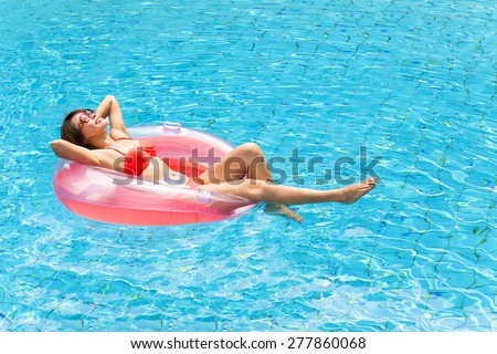 Young woman relaxing in swimming pool - stock photo
