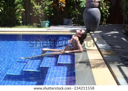 Young woman relaxing in the beautiful swimming pool - stock photo