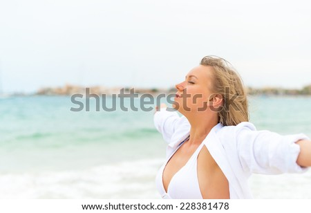 Young woman relaxing near the sea. Space for your text. - stock photo