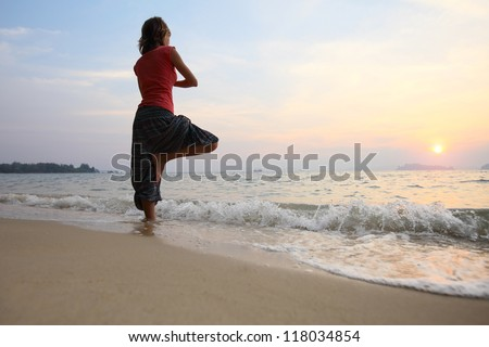Young woman relaxing on a beach at sunset - stock photo
