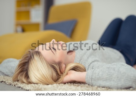 Young woman relaxing on a carpet in her living room lying on her back staring up into the air daydreaming - stock photo