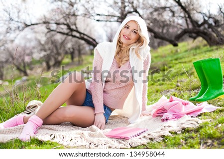 Young woman relaxing on grass with tablet and smiling