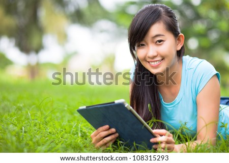 Young woman relaxing on grass with tablet and smiling at camera