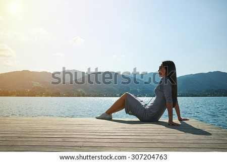young woman relaxing on moorage and looking at beautiful view