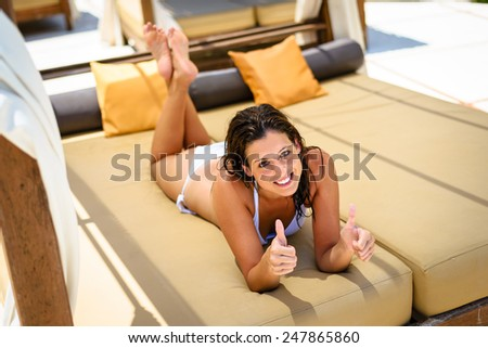 Young woman relaxing on outdoor chaise longue at resort poolside. Brunette caucasian girl in white bikini enjoying summer vacation for resting and relax. - stock photo