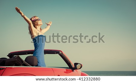 Young woman relaxing on the beach. Girl having fun in red cabriolet against toned sky background. Summer vacation and travel concept - stock photo