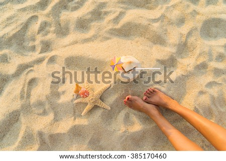 young woman relaxing on the beach with coconut, starfish  and seashell - stock photo