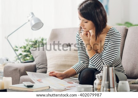 Young woman relaxing on the couch in her living room at home, she is browsing a magazine and having a break