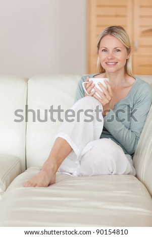 Young woman relaxing on the couch with a cup of coffee