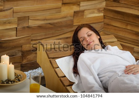 Young woman relaxing on wooden chair at luxury spa