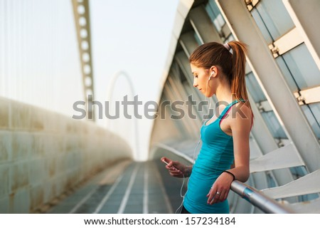 Young woman relaxing outdoors on a modern bridge while listening to music. - stock photo
