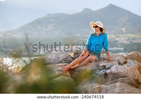 Young woman relaxing outdoors on summer vacation and mountain background - stock photo