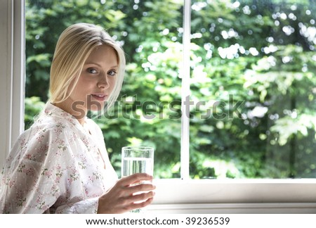 young woman relaxing with a glass of water - stock photo