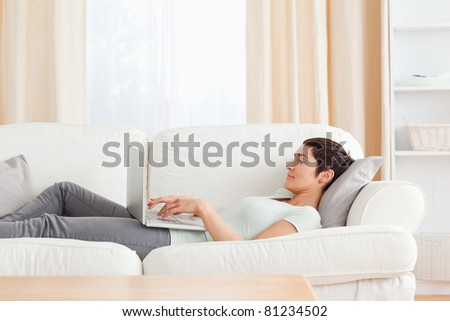 Young woman relaxing with a laptop in her living room