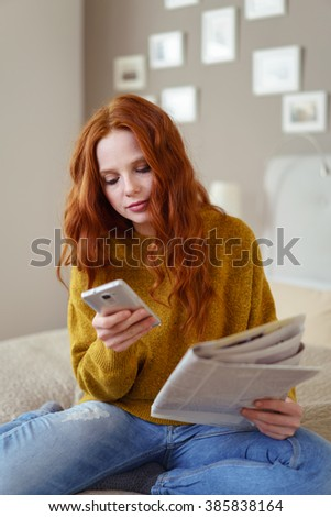 Young woman relaxing with a newspaper on her bed taking a call or reading an sms on her mobile phone - stock photo