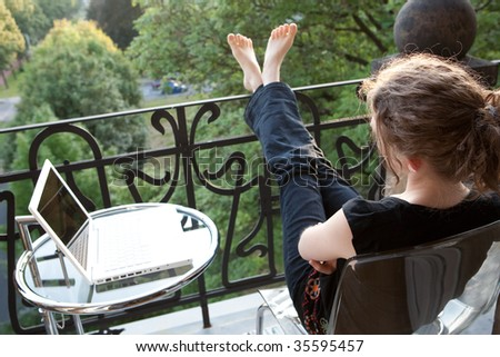 young woman relaxing with a white modern laptop computer on a balcony in art nouveau - stock photo