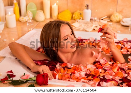Young woman relaxing with rose petals  bath in spa saloon.  - stock photo