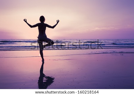 Young woman relaxing with yoga on the beach at sunset - stock photo
