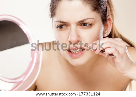 young woman remove hair from her mustache using tweezers - stock photo