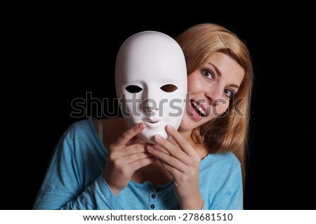 young woman removing plain white mask from her face - stock photo