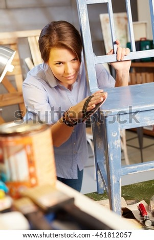 Young woman renewing chair, grinding.