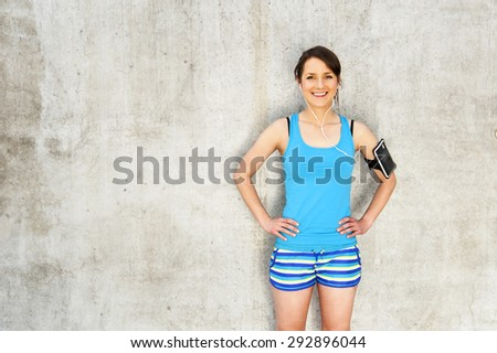 young woman resting after run by the wall in city with big smile. in blue sportswear. listing music.