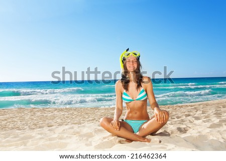 Young woman resting after snorkling sitting on white sand and smiling - stock photo