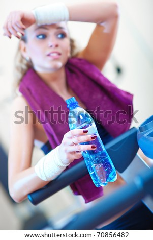 Young woman resting after training. Focus on drink.