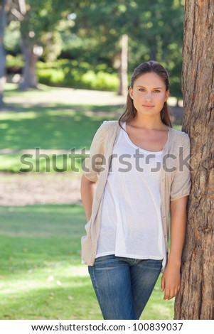 Young woman resting against a tree