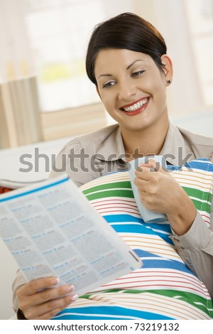 Young woman resting at home wrapped in blanket, reading newspaper and drinking tea.? - stock photo