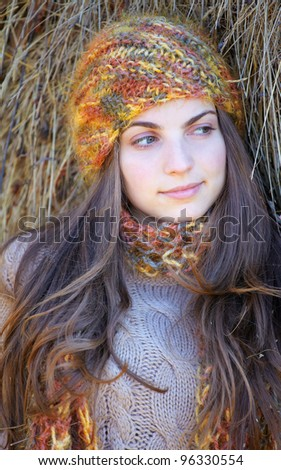 Young woman resting at the shade of a haystack in the countryside. - stock photo