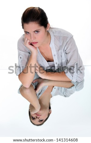 Young woman resting her chin on her hand, reflected underneath in a mirrored surface - stock photo