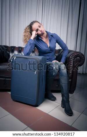 Young woman, resting her head on a suitcase, weary from traveling,Italy