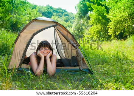 Young woman resting in a tent on the nature - stock photo