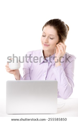 Young woman resting in front of computer enjoying music in earphones with closed eyes, relaxing with cup of coffee - stock photo