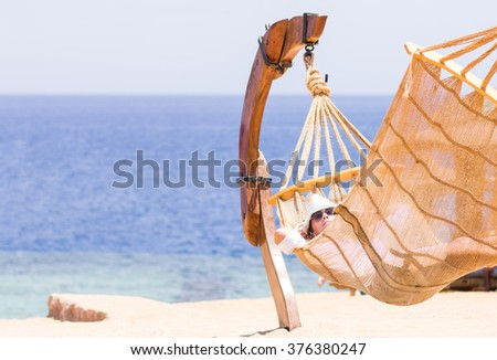 Young woman resting in hammock near the sea or ocean. Travelling beach vacation background with copy space