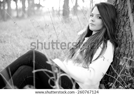 Young Woman Resting In Park - This is a black and white shot of a beautiful young woman sitting in some tall grass next to a tree enjoying the nice weather. Shot with a shallow depth of field. - stock photo