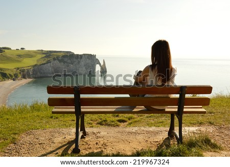 young woman resting on a bench on top of a cliff in Etretat, Normandy, France. - stock photo