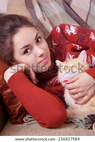 Young woman resting on a sofa with a red cat - stock photo