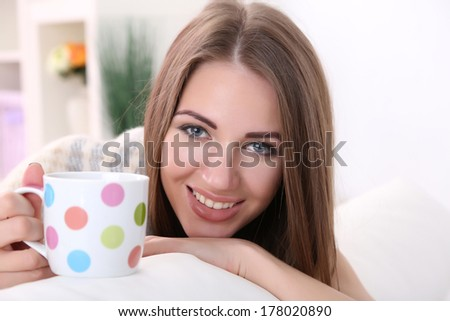 Young woman resting with cup of hot drink on sofa at home - stock photo