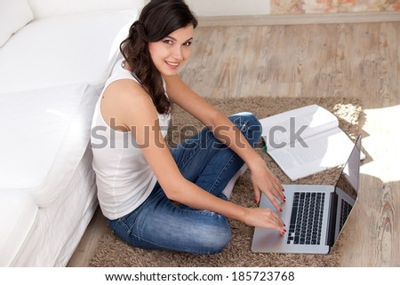 Young woman resting with notebook on floor near sofa, at campus - stock photo