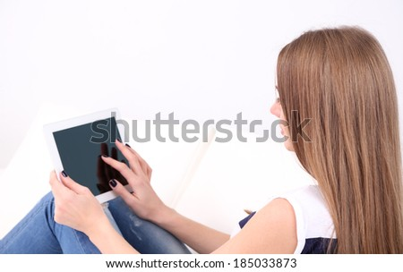 Young woman resting with tablet on sofa at home